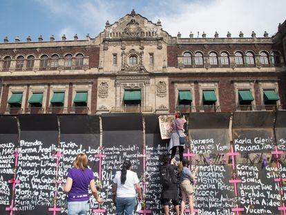 La valla en el perímetro del Palacio Nacional de México, intervenida con nombres de víctimas de feminicidio.