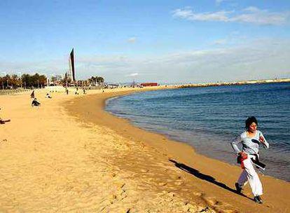 Una mujer corre por una playa de Barcelona