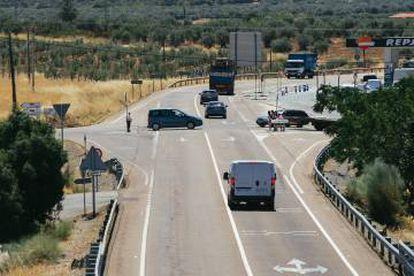 Varios vehículos circulan por la N-435 a la entrada de Almendral, donde los peatones aguardan para cruzar la carretera.