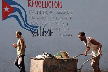 Un hombre empuja una carretilla junto a un cartel alusivo a la revolución en La Habana.