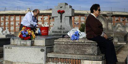 Un hombre limpia una tumba en el cementerio de La Almudena de Madrid.