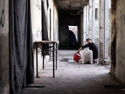 Un migrante mientras utiliza el agua que los voluntarios de la No Name Kitchen proporcionan a diario en Serbia.
