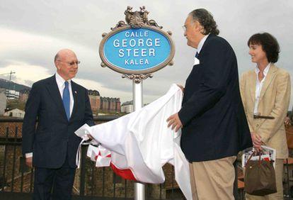 El hijo de Steer, George Barton (a la izquierda), y el alcalde de Bilbao, Iñaki Azkuna, descubren la placa de la nueva calle bilbaína junto a la nieta del periodista, Sophie.