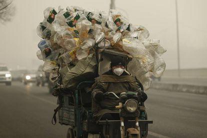 Un motorista conduce su motocarro por Shangháilleva repleto de botellas de plástico para ser recicladas.