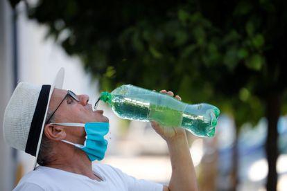 Un hombre se quita la mascarilla para beber agua en mayo en Córdoba.