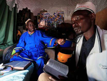 El obispo Bernard Onyango Swa, de la Iglesia Roho Israel de África Oriental, junto al pastor Caleb Wesonga en su casa del suburbio de Kibera, en Nairobi, durante el servicio del Domingo de Ramos. Están prohibidas las reuniones religiosas por el coronavirus en Kenia.