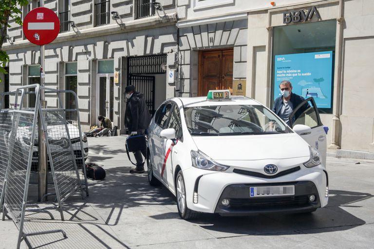 Un taxista con mascarilla deja a un pasajero en una calle de Madrid.