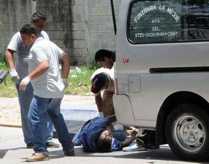 Trabajadores de una funeraria recogen a una víctima en San Pedro Sula.