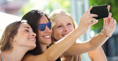 Un grupo de mujeres se hace un 'selfie' con su móvil.