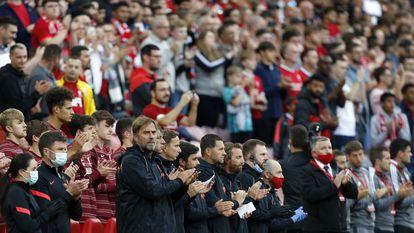 Juergen Klopp y sus asistentes aplauden en la banda durante el homenaje a Michael Robinson en Anfield.