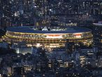 This picture shows the National Stadium, the main venue for the Tokyo 2020 Olympic and Paralympic Games, lit up at dusk in Tokyo on July 16, 2021. (Photo by Charly TRIBALLEAU / AFP)