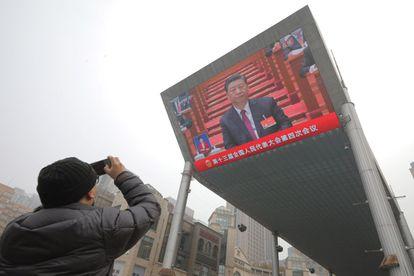 Un hombre fotografía una pantalla que muestra un discurso de Xi Jinping en Beijing.