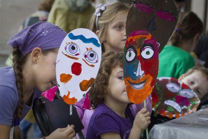 Niños enseñan las máscaras que han fabricado en el taller Cara a Cara, en el paseo de Picasso.