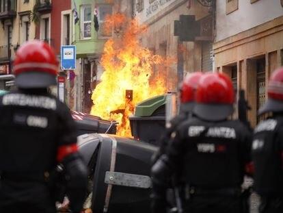 Agentes de la Ertzaintza observan la quema un contenedor durante los altercados producidos en una manifestación en febrero pasado en Bilbao.