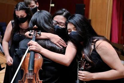 Los miembros de la Orquesta del Encuentro se abrazan al concluir su último concierto en el Auditorio Alfredo Kraus de Las Palmas de Gran Canaria.