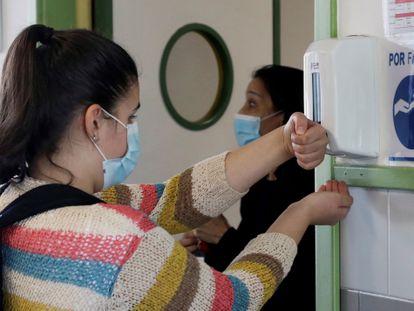 Una alumna del instituto de Sar de Santiago de Compostela se desinfecta.