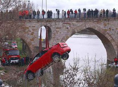 Varios curiosos observan las labores de recuperación del vehículo que cayó al río Duero en Zamora.