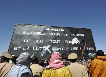 """El alcalde de Gao tapa un cartel yihadista donde se lee: """"Al Hesba, juntos por el placer de Dios todopoderoso y la lucha contra los pecados""""."""