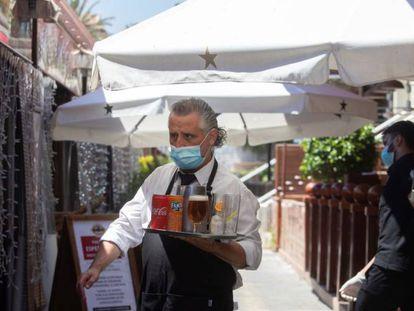 Un camarero lleva su pedido a unos clientes a una de las terrazas del Puerto Olímpico de Barcelona.