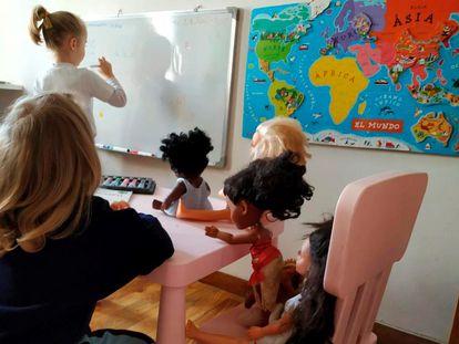 Dos niñas juegan con sus muñecas a que siguen yendo al colegio durante el confinamiento.