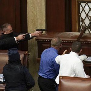 <br /> La policía del Capitolio de los Estados Unidos con armas en la mano observa cómo los manifestantes intentan ingresar a la sesión en la sala principal del Capitolio