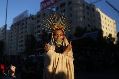 Una mujer realiza una acción artística durante una masiva conmemoración del Día Internacional de la Mujer, en Santiago el 8 de marzo de 2021.