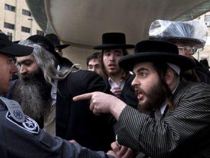 Un judío ultraortodoxo señala a un policía durante una protesta en Jerusalén.
