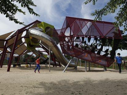 Varos niños juegan este viernes en el parque infantil del Dinosaurio del Manzanares, en el Parque Lineal a la altura de Villaverde.