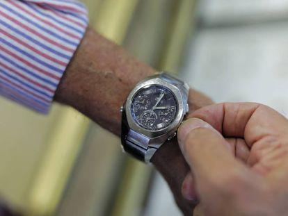 Un hombre mueve la manecilla del reloj para cambiar la hora, en Madrid.