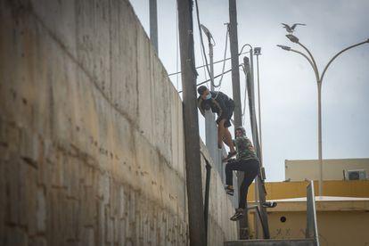 Dos jóvenes se escapan el jueves de las naves de El Tarajal, en Ceuta, cuando iban a ser trasladados en un autobús de la Guardia Civil.