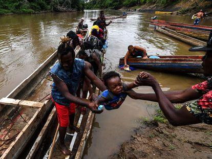 Migrantes llegan en bote a La Peñita en Panamá.