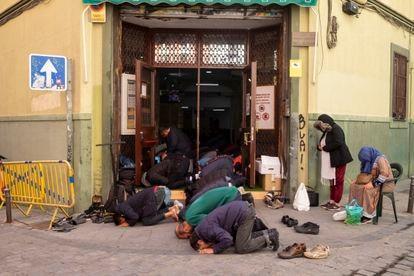 Creyentes musulmanes rezando el viernes 21 de febrero en la puerta de la mezquita y centro islámico Baitul Mukarram, en Lavapiés, en el centro de Madrid.