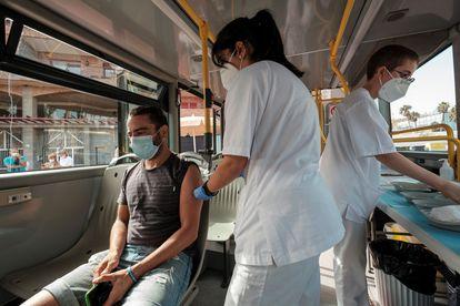 Una enfermera vacuna a un hombre en la 'Vacuguagua', un autobús que equipado que recorre playas y pueblos de Gran Canaria (hay otro en Tenerife) para vacunar a personas que aún no lo hayan sido.
