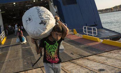 Refugiados del campamento incendiado de Moria en Lesbos desembarcan en un ferry en el puerto de Lavrio para ser trasladados a otro asentamiento en la Grecia continental.
