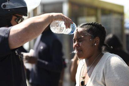 Un policía lava la cara de una mujer que fue alcanzada por spray de pimienta, ayer en Baltimore.