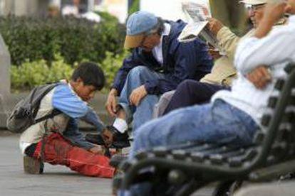 Un niño lustra botas trabaja en una calle de Quito (Ecuador). EFE/Archivo