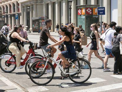 Gente en bicicleta y a pie cruza una calle en la Plaza de Cataluña.