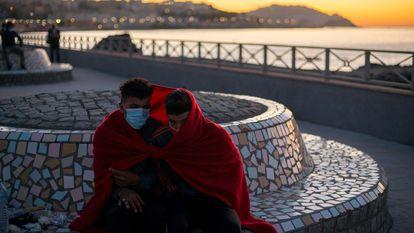 Dos jóvenes inmigrantes se protegen del frío a primera hora de la mañana del 19 de mayo cerca de la playa ceutí de El Tarajal.