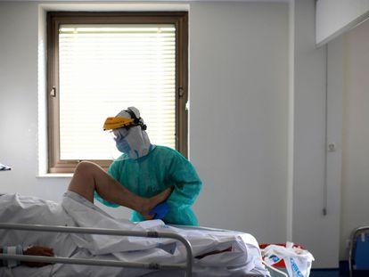 Un fisioterapeuta con traje protector atiende a un paciente con coronavirus en la Unidad de Cuidados Intensivos (UCI) del Hospital Ramón y Cajal de Madrid en octubre del año pasado.