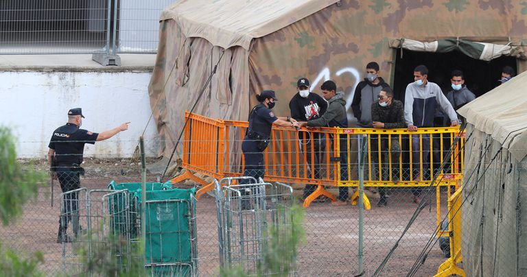 Varios inmigrantes hablaban ayer con agentes de la Policía Nacional en el campamento de atención temporal del antiguo polvorín de Barranco Seco.