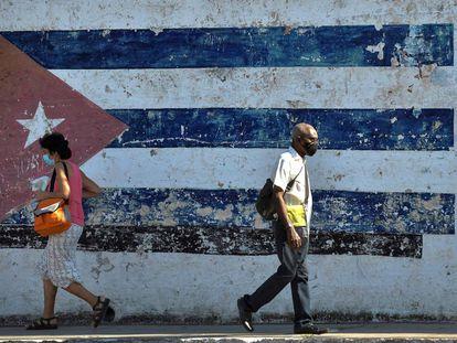 Dos personas caminan cerca de un mural con la bandera cubana en La Habana, el pasado 16 de abril.