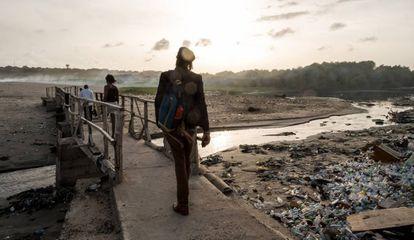 Los activistas de Plastic Punch Henry Amankwah, Fatoumata Jammeh y Richmond 'Legacy' Kennedy Quarcoo caminan hacia una playa contaminada en Accra, Ghana, en abril de 2019.