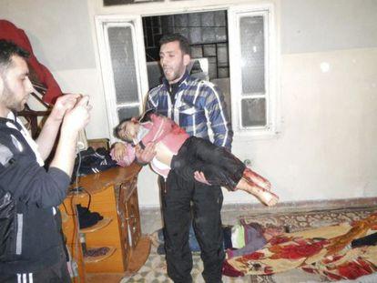 Imagen facilitada por la oposición siria de un hombre con el cadáver de un niño en brazos, asesinado en Karm al-Zeitoun, cerca de Homs.