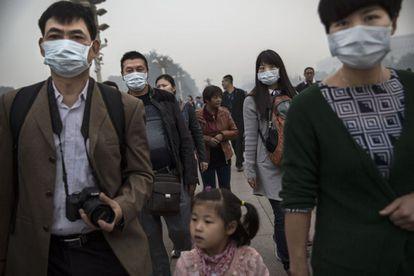 Varias personas con mascarillas en la plaza de Tiananmen de Pekín.