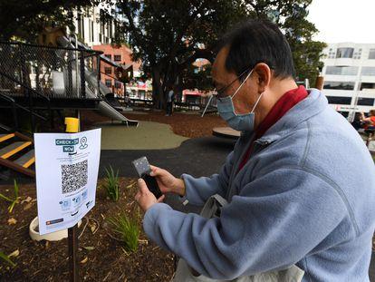 Un hombre escanea un código QR para entrar en un parque en Melbourne, Australia.
