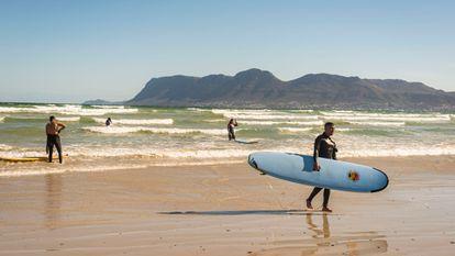 Yusuf y Atyab, dos surferos principiantes, salen del agua en la playa de Muizenberg, en Sudáfrica, el 12 de diciembre de 2020.