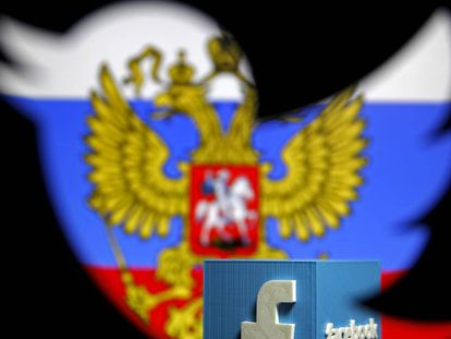Una bandera rusa y un logo de Facebook vistos a través de un agujero con el logo de Twitter.