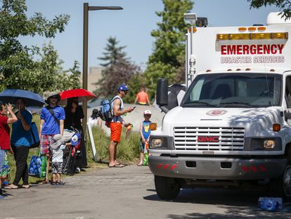 Un vehículo de emergencias junto a la cola de personas que esperan para entrar en un parque acuático y combatir el calor, en Calgary (Canadá).