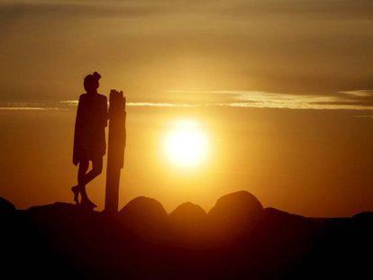 Una mujer disfruta de la llegada del verano con la puesta de sol