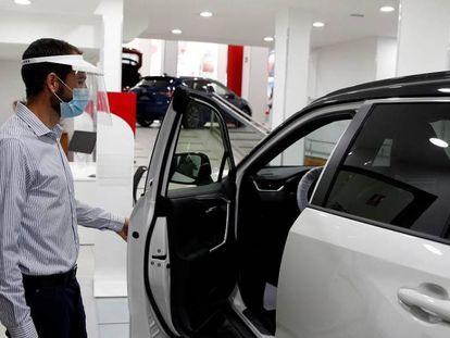 Una persona abre la puerta de un vehículo de muestra en un concesionario, en Madrid.